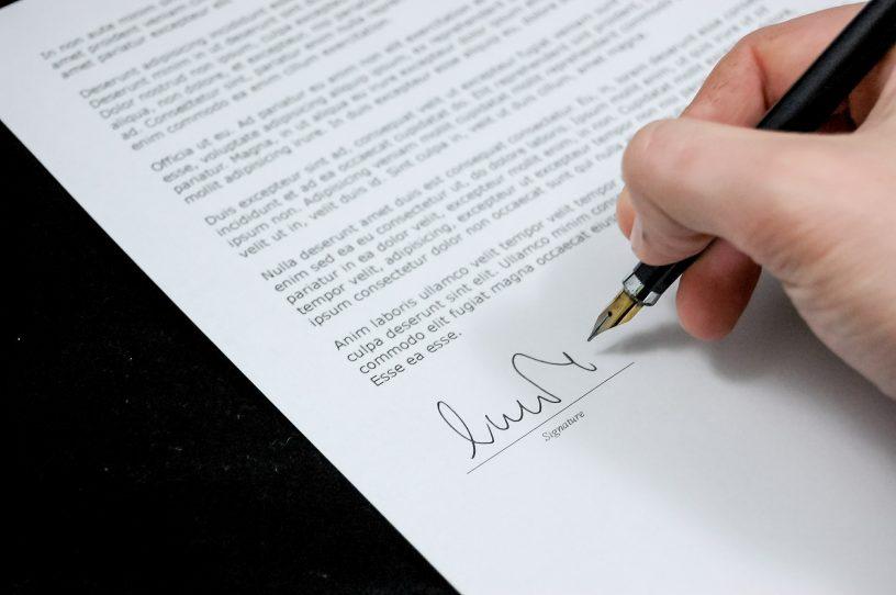 Eine Hand unterschreibt einen Vertrag.