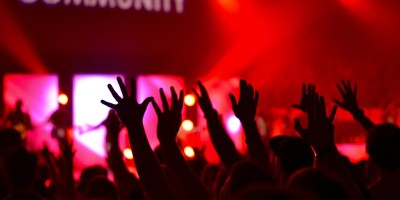 Personen stehen vor einer Bühne und strecken die Hände nach oben.