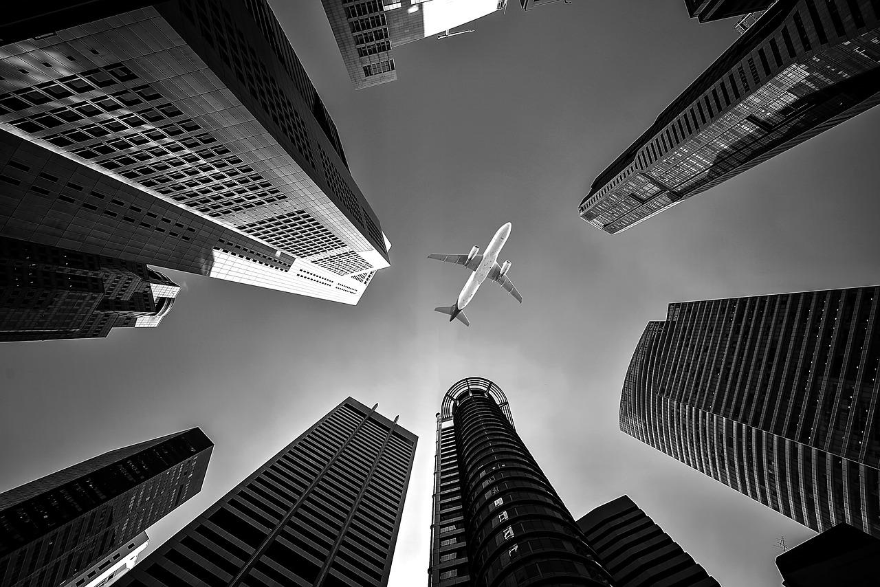 Flugzeug am Himmel und Hochhäuser.