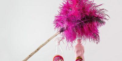 Pinker Staubwedel und zwei Reinigungsmittel in Flaschen.
