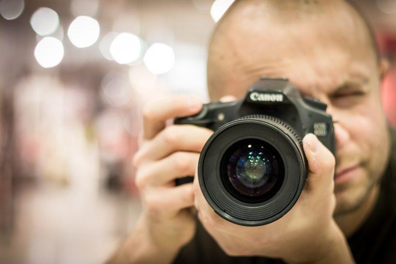 Mann macht ein Foto mit einer Kamera.